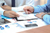 Business colleagues working together and analyzing financial figures on a graphs — Stock Photo