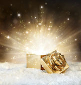 Magic shining of christmas gift - golden stardust and snow — Stock Photo