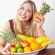 Young healthy beautiful woman with a bowl of fresh exotic fruit — Stock Photo #51862877