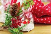 Candle and berries on pine brunch with christmas fabric — Stock Photo