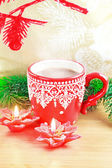 Cup of hot cocao with red poinsettia candle and pine — Stock Photo