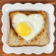 Slice of cereal toast bread with cut out heart shape full egg on white plate — Stock Photo #62452747