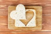 Slice of cereal toast bread with cut out heart shape on wooden cutting board — Stock Photo