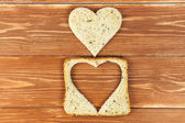 Slice of cereal toast bread with cut out heart shape on wooden background — Stock Photo
