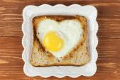 Slice of cereal toast bread with cut out heart shape full egg on white plate — Stock Photo