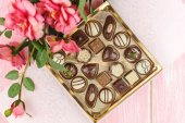 Box with chocolates and pink flowers. Selective focus. — Stock Photo