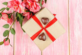 Gift box with red ribbon, candy and pink flowers. Selective focus. — Stock Photo