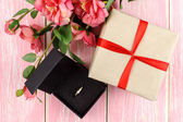 Gift with red ribbon, ring in box and pink flowers. Selective focus. — Zdjęcie stockowe