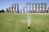 Grass Sprinklers wtih Roman Aqueduct — Stock Photo