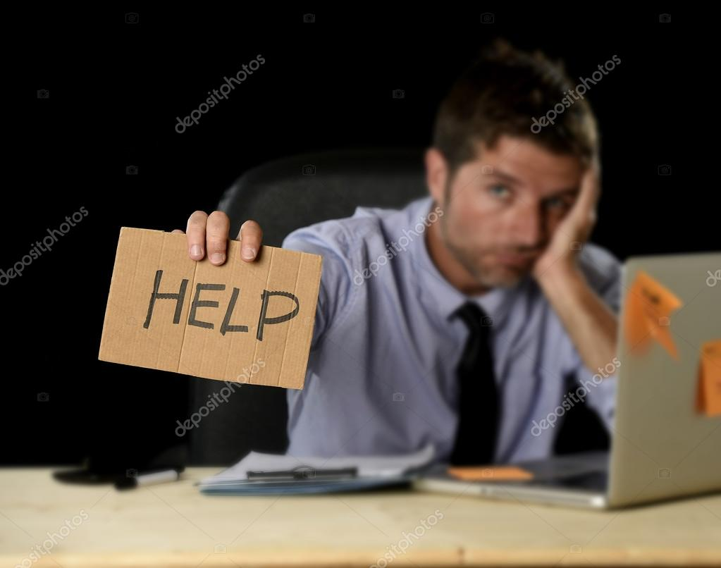 tired desperate businessman in stress working at office computer tired desperate businessman in stress working at office computer desk holding sign asking for help
