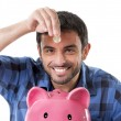 Young happy man holding coin putting it into pink piggy bank — Stock Photo #52121223