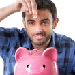 Young happy man holding coin putting it into pink piggy bank — Stock Photo #52121255