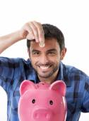 Young happy man holding coin putting it into pink piggy bank — Стоковое фото