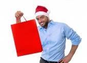 Happy young handsome man wearing santa hat holding red shopping bag — Stock Photo