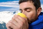 Young attractive man outdoors drinking cup of coffee or tea in cold winter snow mountain at xmas holiday — Stock Photo