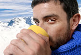 Young attractive man outdoors drinking cup of coffee or tea in cold winter snow mountain at christmas holiday — Stock Photo