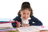 Sweet happy latin child sitting on desk doing homework and smiling — Foto Stock