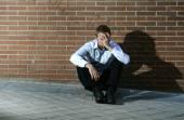 Businessman who lost job lost in depression sitting on city street corner — Stock Photo