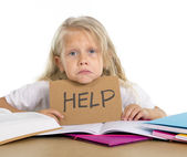 Sweet little school girl holding help sign in stress with books and homework — Stock Photo