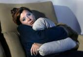 Woman sitting on couch holding pillow against chest in stress and depression — Foto de Stock