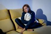 Young depressed woman on couch with pillow cushion crying alone in stress  — Stock Photo