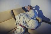 Young sick woman sitting on couch wrapped in duvet and blanket feeling miserable — Stock Photo