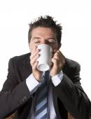 Addict businessman in suit and tie holding cup of coffee as maniac in caffeine addiction — Stock Photo