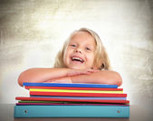 Cute schoolgirl with blonde hair sitting happy on desk laughing and smiling — Stock Photo