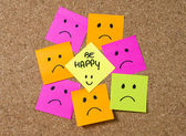 Smiley post it note on corkboard in happiness versus depression concept — Stock Photo