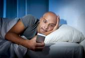 Young cell phone addict man awake at night in bed using smartphone — Foto Stock