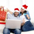 Young attractive Hispanic couple in love online Christmas shopping with computer — Photo #56593321
