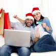 Young attractive Hispanic couple in love online Christmas shopping with computer — Photo #56593339