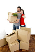 Happy couple moving together in a new house unpacking cardboard boxes — Stock Photo