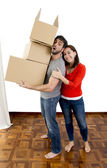 Happy couple moving together in a new house carrying cardboard boxes  — Stock Photo
