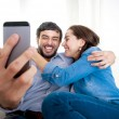 Nice attractive young couple sitting together in sofa couch taking selfie photo with mobile phone — Stock Photo #56843839