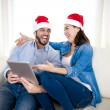 Young attractive Hispanic couple in love online Christmas shopping digital tablet — Stock Photo #56843941