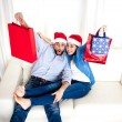 Young happy couple in Santa hat on Christmas holding shopping bags with presents  — Stock Photo #56846995