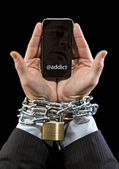 Hands of businessman addicted to work chain locked in mobile phone addiction — Stock Photo