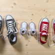 Three pair of shoes in father big, mother medium and son or daughter small kid size in family togetherness concept — Stock Photo #60202747