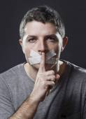 Attractive young man with mouth sealed on duct tape to prevent him from speaking — Stock Photo