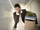 Sad depressed businesswoman carrying cardboard box fired from Job — Stock Photo