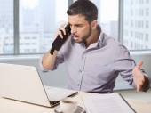 Businessman at office in front of skyscraper window view talking upset on the phone working with computer — Stock Photo