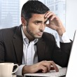Attractive Hispanic businessman working with computer looking stressed and worried facing work issue — Stock Photo #62114537