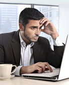 Attractive Hispanic businessman working with computer looking stressed and worried facing work issue — Stockfoto
