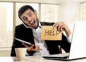 Businessman in stress holding help sign multitasking overwhelmed in business district office — ストック写真