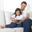 Young father sitting on couch with sweet little daughter using digital tablet smiling happy — Stock Photo #62475257