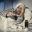 Sick man lying in bed suffering cold and winter flu virus having medicine and tablets — Stock Photo #62478267