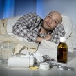Sick man lying in bed suffering cold and winter flu virus having medicine and tablets — Stock Photo #62478861