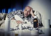 Sick man lying in bed suffering cold and winter flu virus having medicine and tablets — Stockfoto