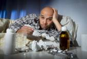 Sick man lying in bed suffering cold and winter flu virus having medicine and tablets — ストック写真